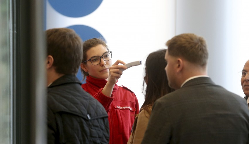Austrian rescue personnel checks the body temperature of persons during an informal meeting of oil ministers of the Organization of Petroleum Exporting Countries, OPEC, at the OPEC headquarters in Vienna, Austria, Wednesday, March 4, 2020. (AP Photo/Roland Zak)