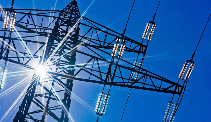A high-voltage electricity pylons against blue sky and sun rays.