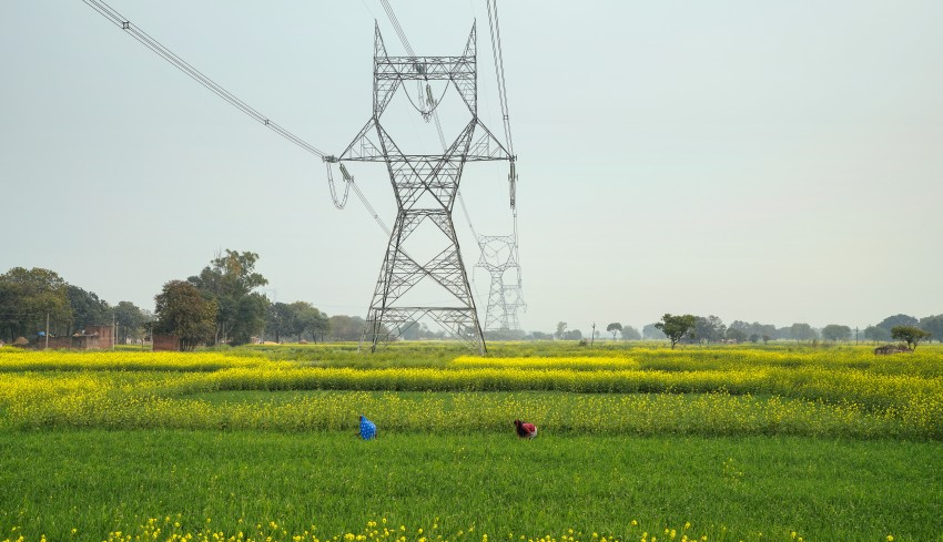 High voltage electricity Transmission Towers of National Grid passing through green mustard fields , Uttar Pradesh, India
