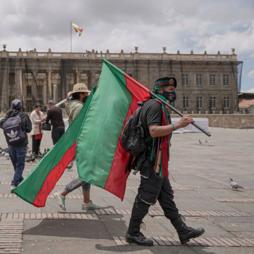 An indigenous man holds a flag at Plaza de Bolivar during a general strike against social and economic policies.
