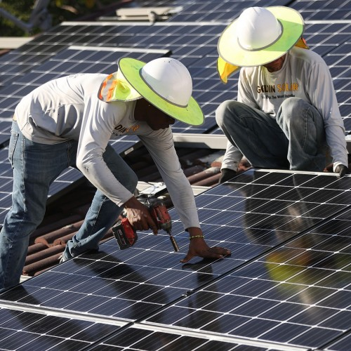 Workers install a solar panel system on the roof of a home in Palmetto Bay, Florida, on Jan. 23, 2018.