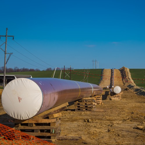 A pipeline under construction in farmland.